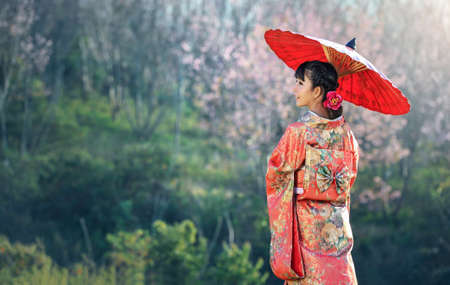 Photo pour Asian woman wearing traditional japanese kimono, sakura background - image libre de droit