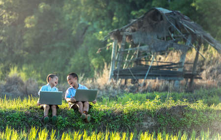 Photo for Two boys studying by online learning with laptop at outdoor, countryside of Thailand - Royalty Free Image