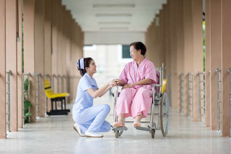 Photo pour Senior woman in wheelchair talking to a nurse in a hospital - image libre de droit