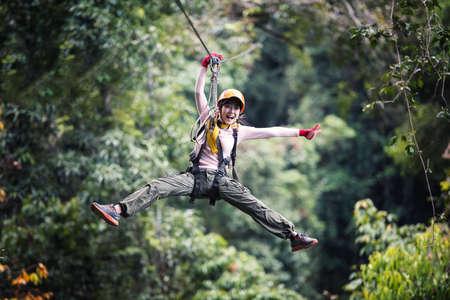Photo pour Woman Tourist Wearing Casual Clothing On Zip Line Or Canopy Experience In Laos Rainforest, Asia - image libre de droit