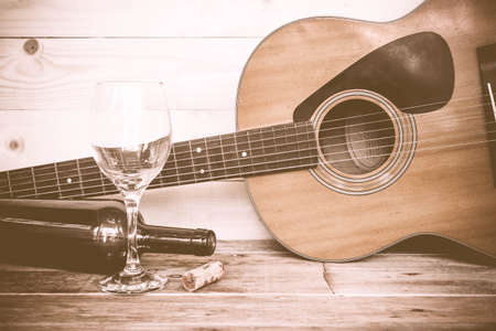 Photo for vintage Guitar with wine bottle and glass on the old wood floor. - Royalty Free Image