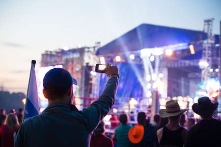 Photo for silhouette of young man taking pictures rock concert on the phone open fest - Royalty Free Image