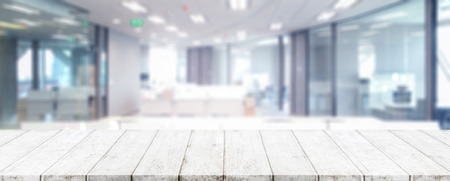 Photo for Wood table top and blurred bokeh office interior space background - can used for display or montage your products. - Royalty Free Image