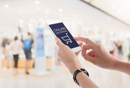 Photo for Woman hands holding and using smartphone with online shopping screen on blurred shopping mall interior background. Ecommerce concept. - Royalty Free Image