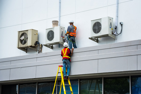 Foto de Air Conditioning Technician are servicing air conditioners. - Imagen libre de derechos