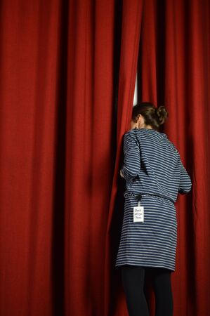Photo for Woman with a backstage looking over the red curtains on a stage - Royalty Free Image