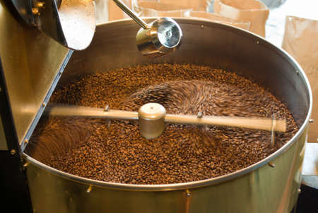 Foto de the process of roasting coffee in a large roasting pan mechanical - Imagen libre de derechos