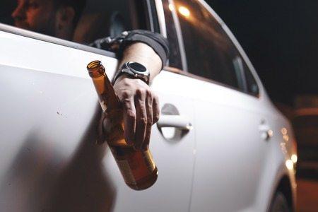 Photo pour Drunk young man drives a car with a bottle of beer. This is a campaign picture of Dont Drink for Drive. - image libre de droit