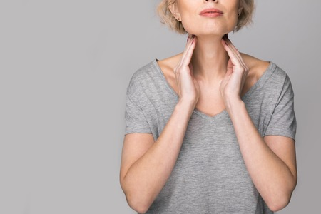 Foto de Female checking thyroid gland by herself. Close up of woman in white t- shirt touching neck with red spot. Thyroid disorder includes goiter, hyperthyroid, hypothyroid, tumor or cancer. Health care. - Imagen libre de derechos