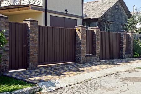 Foto de Gray brown iron fence in front of asphalt road - Imagen libre de derechos