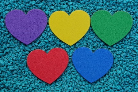 Photo pour a row of colored hearts on blue small stones - image libre de droit