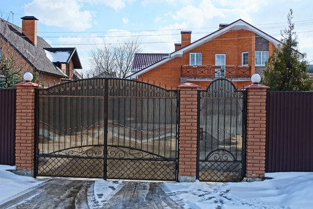 Photo for closed brown gates and part of the fence in the street near the road in the snow - Royalty Free Image