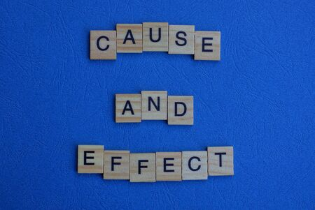 Foto de the phrase cause and effect of brown wooden letters lies on a blue table - Imagen libre de derechos