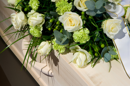 Photo for A coffin with a flower arrangement in a morgue - Royalty Free Image