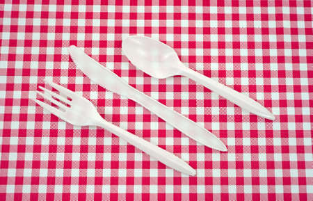 A set of plastic silverware arranged on a red and white picnic tablecloth.