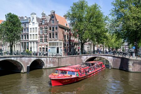 Foto de Amsterdam canal boat PC HOOFT of City Sightseeing Amsterdam at Keizersgracht/ Leidsegracht intersection. - Imagen libre de derechos