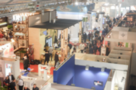 Foto de Defocused background of a trade show with people visiting the commercial exhibition. Intentionally blurred post production for bokeh effect - Imagen libre de derechos