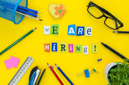 Photo for WE ARE HIRING CONCEPT ON yellow work place, office background with supplies - Royalty Free Image