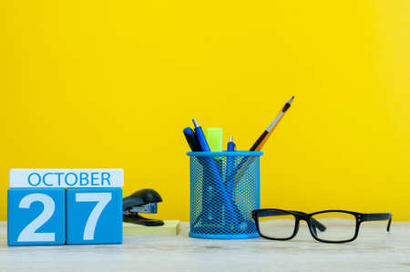 Foto de October 27th. Day 27 of october month, wooden color calendar on teacher or student table, yellow background . Autumn time - Imagen libre de derechos