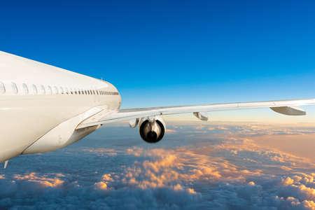Foto de Passenger jet plane in the blue sky, unique side view. Aircraft flying above the cumulus clouds. Airplane travel concept - Imagen libre de derechos