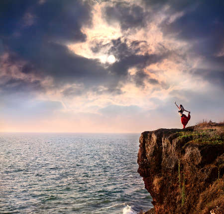 Photo pour Beautiful woman doing natarajasana dancer yoga pose on the cliff near the ocean with dramatic sky at background in India - image libre de droit