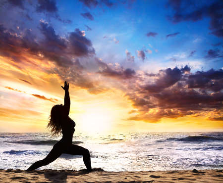 Photo for Beautiful Woman silhouette doing virabhadrasana I warrior pose on the sand beach and ocean nearby at sunset background in India, Goa - Royalty Free Image