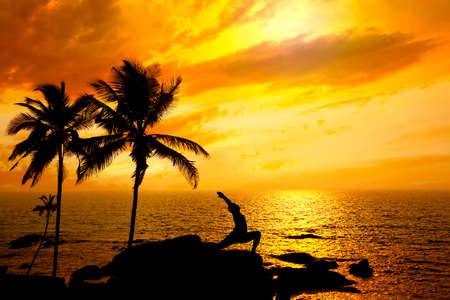 Yoga virabhadrasana I warrior pose by Man in silhouette with palm tree nearby outdoors at ocean and sunset background. Vagator beach, Goa, India. Free space for text