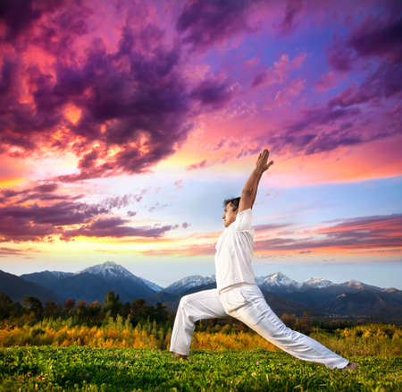 Photo for Yoga virabhadrasana I warrior pose by Indian Man in white cloth in the morning at mountain background - Royalty Free Image