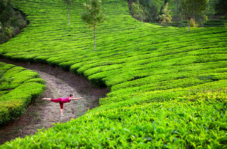 Photo pour Yoga virabhadrasana III warrior pose by woman in red cloth on tea plantations in Munnar hills, Kerala, India - image libre de droit