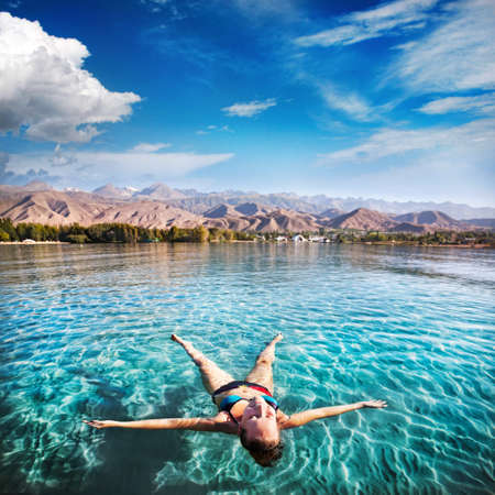 Foto de Woman laying like a star in Issyk Kul lake at mountains background in Kyrgyzstan, central Asia - Imagen libre de derechos
