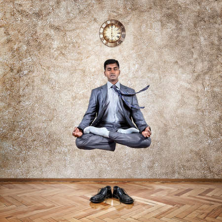 Levitation by Indian businessman in lotus pose in the office near the wall with clock and his shoes on the floor