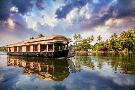 Foto de House boat in backwaters near palms at cloudy blue sky in Alappuzha, Kerala, India - Imagen libre de derechos