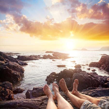 Foto de Woman and man sitting on the rocks near the ocean at cloudy sunset sky - Imagen libre de derechos