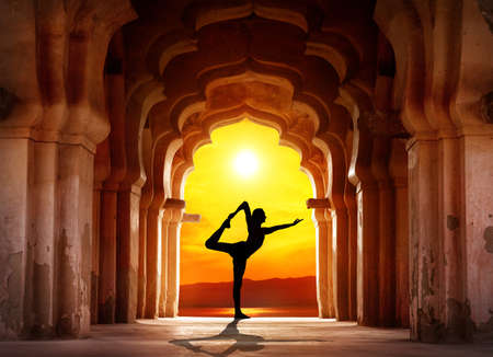Foto de Man silhouette doing yoga in old temple at orange sunset sky background - Imagen libre de derechos