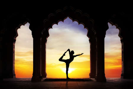 Foto de Man silhouette doing yoga in old temple at orange sunset sky background - Imagen libre de derechos