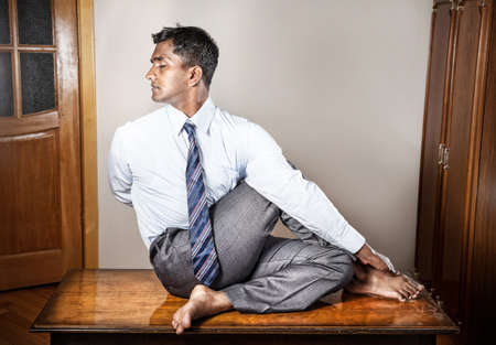 Photo for Indian businessman doing yoga on the table in the office  - Royalty Free Image