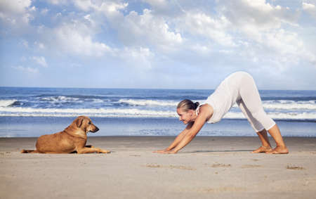 Foto de Woman in white costume doing Yoga and looking at the dog on the beach near the ocean in India - Imagen libre de derechos