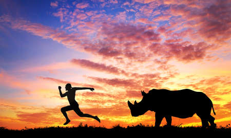 Photo for Man running away from rhino at sunset in savanna - Royalty Free Image