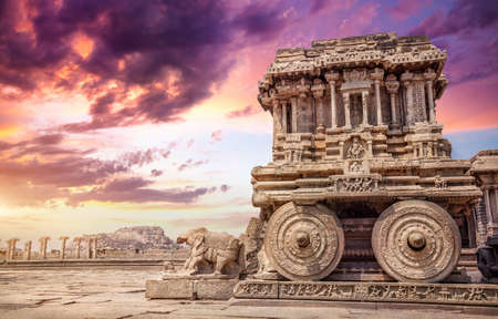 Photo for Stone chariot in courtyard of Vittala Temple at sunset purple sky in Hampi, Karnataka, India - Royalty Free Image