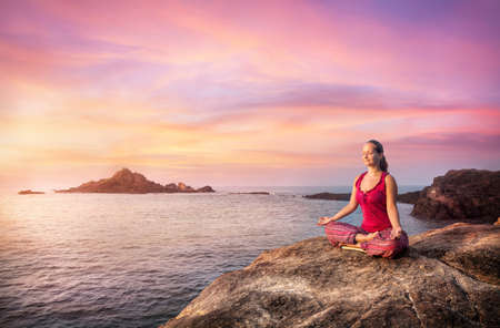 Photo pour Woman doing meditation in red costume on the stone near the ocean in Gokarna, Karnataka, India - image libre de droit