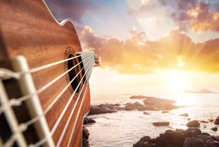 Photo for Guitar player at seascape sunset background - Royalty Free Image
