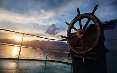 Photo pour Wooden wheel on the ship at sunset on Issyk Kul lake - image libre de droit