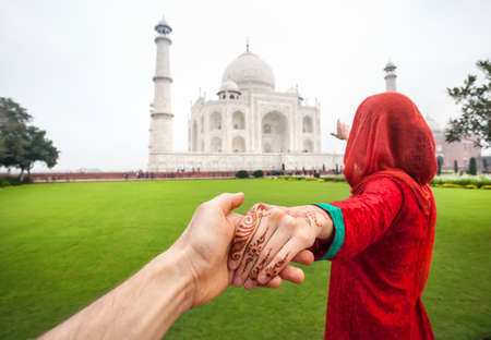 Photo pour Woman in red Indian costume holding her friend by hand and pointing to Taj Mahal in Agra, Uttar Pradesh, India - image libre de droit