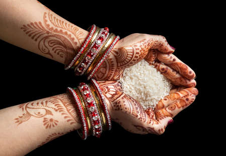 Photo pour Woman hands with henna holding rice isolated on black background with clipping path - image libre de droit