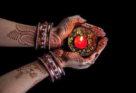 Photo for Woman hands with henna holding candle isolated on black background with clipping path - Royalty Free Image