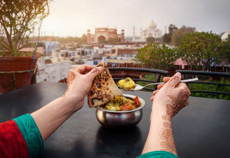 Photo for Woman eating traditional Indian food in rooftop restaurant with Taj Mahal view in Agra, Uttar Pradesh, India - Royalty Free Image