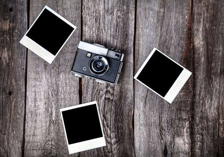 Photo for Old film camera and polaroid photos with space for pictures on the wooden background - Royalty Free Image
