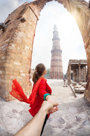 Foto de Woman in red costume leading man by hand to Qutub Minar tower in Delhi, India - Imagen libre de derechos