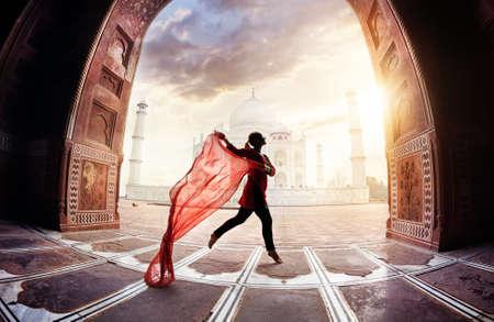 Foto de Woman with red scarf dancing near Taj Mahal in Agra, Uttar Pradesh, India - Imagen libre de derechos