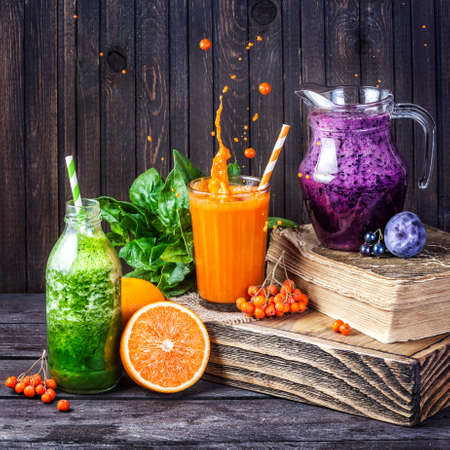 Photo pour Fresh juice and smoothies with berries, fruits and green spinach on wooden background - image libre de droit